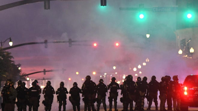 Officers with the New Hanover County Sheriff's Office line up along 3rd. St. after firing tear gas while confronting protestors in downtown Wilmington, N.C., Sunday, May 31, 2020. The protest turned confrontational as protesters and police clashed a day after a peaceful protest was held to show solidarity with George Floyd.