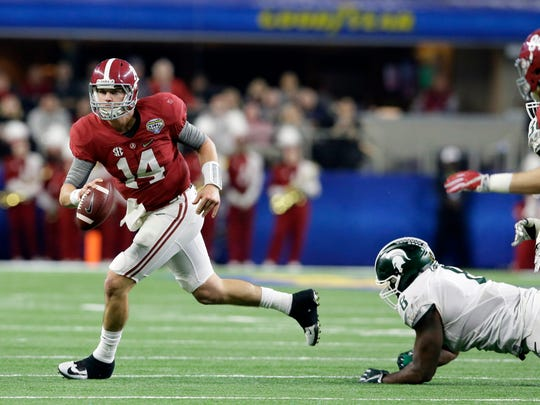 Alabama quarterback Jake Coker (14) escapes the grasp of Michigan State defensive lineman Lawrence Thomas (8) during the first half of the Cotton Bowl NCAA college football semifinal playoff game, Thursday, Dec. 31, 2015, in Arlington, Texas. (AP Photo/LM Otero)