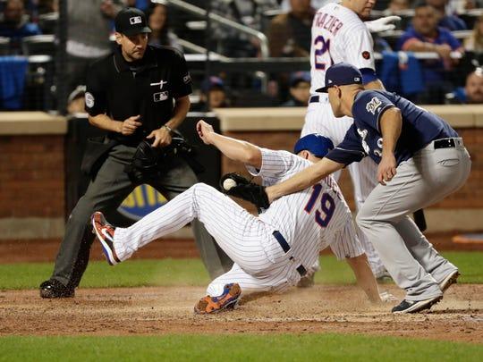 New York Mets' Jay Bruce (19) slides past Milwaukee