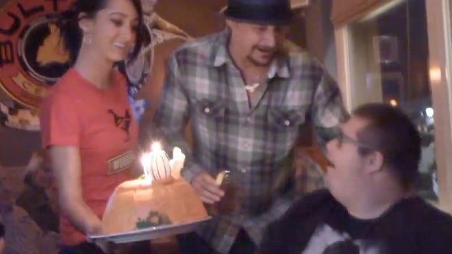 Kid Rock, center, surprises fan Dan McGurk with a birthday party visit on Monday.