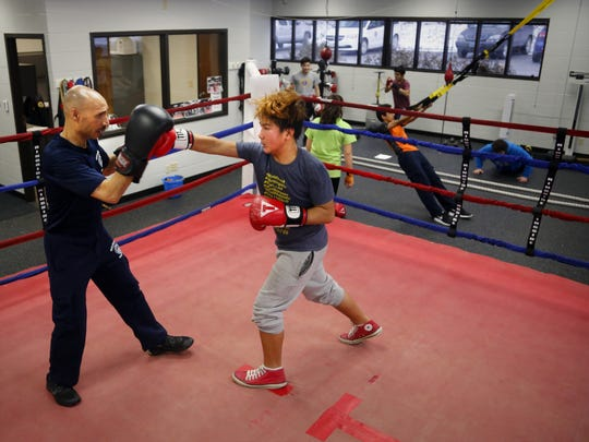 Des Moines Senior Police Officer John Saunders works with Eh Po Thabo, 12, at the Des Moines Police Boxing Club on Thursday, Jan. 26, 2017.