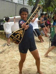 Shanice Devera holds up the third place Manhoben Girls winning paddle in the GKCF/IIAAG paddling series.