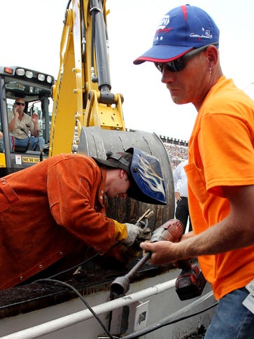 Track officials work to repair a section of the pit