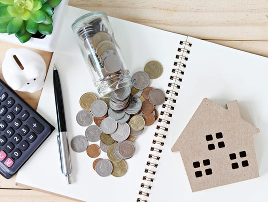 Flat lay or top view of wood house model and coins scattered from glass jar on open blank notebook paper