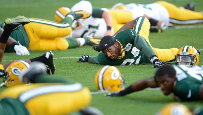 Green Bay Packers cornerback Jarrett Bush stretches out at Saturday's Family Night practice at Lambeau Field.