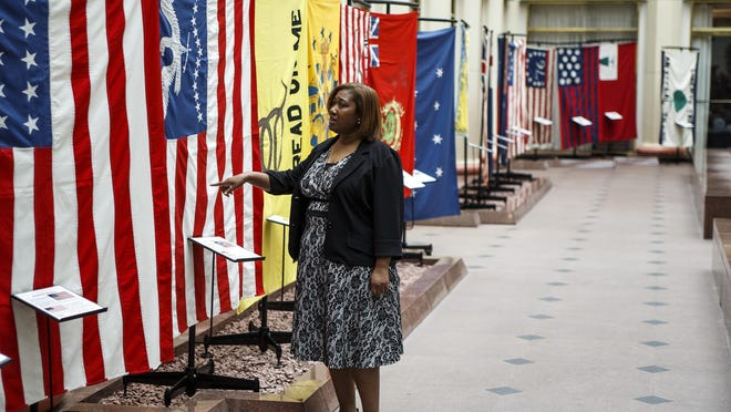 State Rep. Vanessa Lowery Brown, D-Philadelphia, looks at flags after taking the Confederate flag down from a display Tuesday night at the Pennsylvania Capitol East Wing Rotunda fountain area. The flag was returned to the display Wednesday and then ordered removed by Gov. Wolf. The flag is part of the Hanover Area Historical Society's display of flags from different chapters of North American history, Wednesday, June 15, 2016. (Dan Gleiter/PennLive.com via AP)