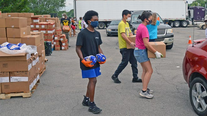 Volunteers Joaquin Fox, from left, Matthew Bailey and Katy Featherston load vehicles with food items including whole chickens during Antioch for Youth and Family's Go Fresh Pop Up Pantry in cooperation with the River Valley Regional Food Bank at Martin Luther King Jr. Community Park on Wednesday, July 1, 2020. The event is held each Wednesday throughout the summer and provides for more than 3,000 people each Wednesday.