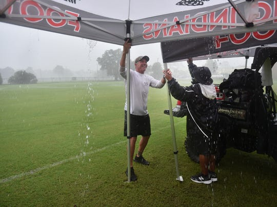 Brian Stolze (left), of Fighting Indians booster club, and Joe Moore, football team chaplain, struggle to hold down canopies as strong gusts of wind and rain wash out the Vero Beach High School football practice Monday morning, July 31, 2017, behind the school.