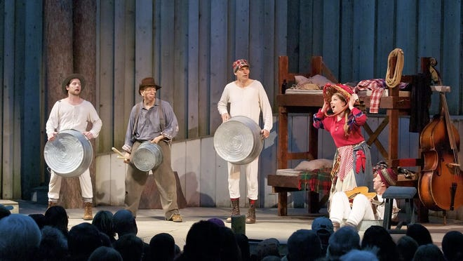"""A Northern Sky Theater audience watches from its seats in the amphitheater at Peninsula State Park as The Kid, played by Pamela Niespodziani, poses as the mail-order bride while Moonlight (Chase Stoeger), Dirty Bob (Doug Mancheski), Slim (Jeffrey Herbst) and Muskrat (Doc Heide, on the floor at far right) contemplate the situation in a scene from """"Lumberjacks in Love."""" Northern Sky and the Wisconsin Department of Natural Resources recently extended their agreement to have the company continue holdings its summer musicals at the park for another 15 years."""