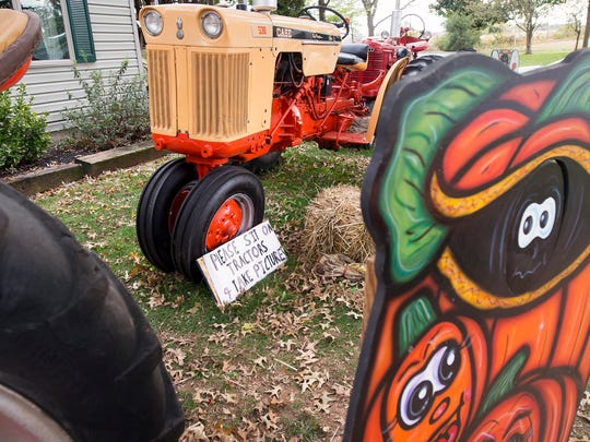 Children are encouraged to sit on the tractors at Pumpkin Hill in Paradise Township.