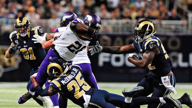 Minnesota Vikings running back Adrian Peterson (28) is tackled by St. Louis Rams strong safety T.J. McDonald (25) during the first half at the Edward Jones Dome on sept. 7, 2014.