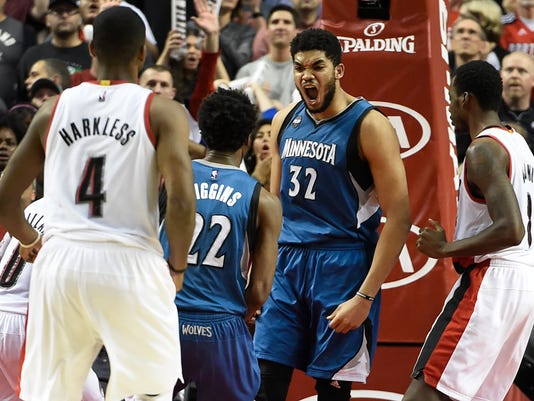 Minnesota Timberwolves center Karl-Anthony Towns (32) celebrates with guard Andrew Wiggins (22) after hitting the game-winning shot during the fourth quarter of an NBA basketball game in Portland, Ore., Saturday, April 9, 2016. The Timberwolves won 106-105. (AP Photo/Steve Dykes)