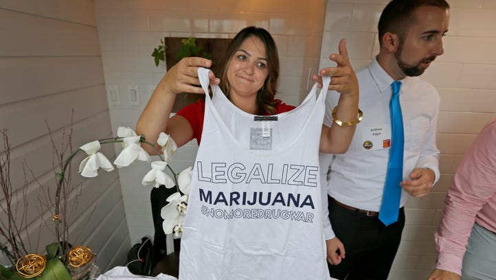 Kaitlyn Boecker, policy coordinator for the Drug Policy Alliance, holds up a T-shirt, during a marijuana industry reception Monday during the Democratic National Convention in Philadelphia.