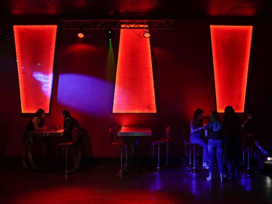 Customers mingle at Lavish Ultra Lounge, a new club, located at 201 E. University Ave., featuring colorful lighting, comfortable seating and popular local DJs.
