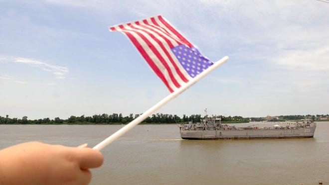 ERIN McCRACKEN / Courier & Press ARCHIVES Laura James, 9, waves an American Flag as she watches the LST 325 cruise down the Ohio River during the opening ceremonies of the Evansville Freedom Festival on Thursday, June 18, 2009. Laura's father Mark James is with he 384th military police detachment in Iraq until next January. and her sister Summer James, 4, led the crowd in the Pledge of Allegiance at the Opening Ceremonies of the Evansville Freedom Festival.