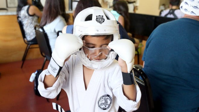 GABE HERNANDEZ/CALLER-TIMES Noah Montes adjusts his helmet as he works on his technique Tuesday at Corpus Christi Downtown Karate. Students from Downtown Karate will be competing in the AAU Junior Olympic Games in Houston.