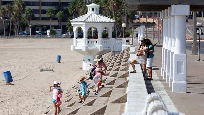 A family walks to McGee Beach on Friday, Aug. 12, 2016, in Corpus Christi.