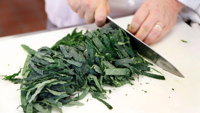 Charles Bertram/Lexington Herald-Leader/TNS Chef Bob Perry slices lacinato kale into ribbons.