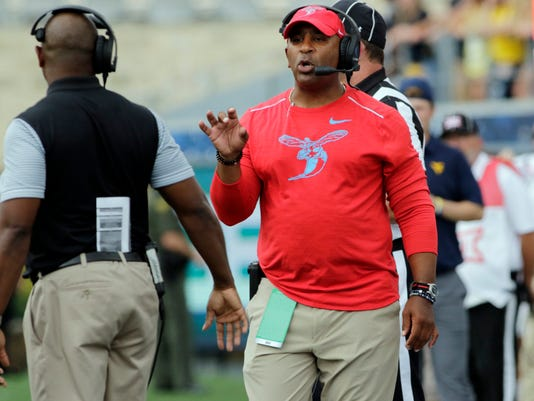 Delaware State head coach Kenny Carter gives instructions his an assistant coach during the first half of an NCAA college football game against West Virginia, Saturday, Sept. 16, 2017, in Morgantown, W.Va. (AP Photo/Raymond Thompson)