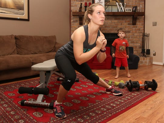"Loryn Wooten works out at home to ""The Master's Hammer and Chisel"" DVD by Beachbody as her son, Lucas, 4, watches."