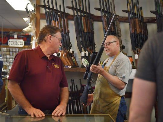 Gary's Gun Shop owner Steve Naatjes, left, and gun smith Steve Hansen show different gun models to Alex Lerdal, far right, Friday at the shop.
