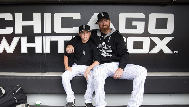 White Sox designated hitter Adam LaRoche (25) sits with his son Drake, 13, in the White Sox dugout at U.S. Cellular Field before a game against the Houston Astros on June 8, 2015, in Chicago.