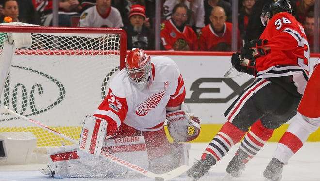 Red Wings goalie Petr Mrazek (34) makes a save against Blackhawks right wing Ryan Hartman (38) during the first period Tuesday in Chicago.