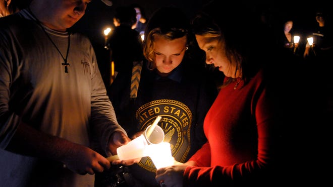 Nick Bush, left, Savannah Hardage and Jennifer Holland help each other light their candles Wednesday night as the candlight vigil at the end of the Navarre Pier got underway. The vigil was held to honor the memory of the men who died in Tuesday night's Blackhawk helicopter crash east of the Navarre Beach Bridge during a training exercise.