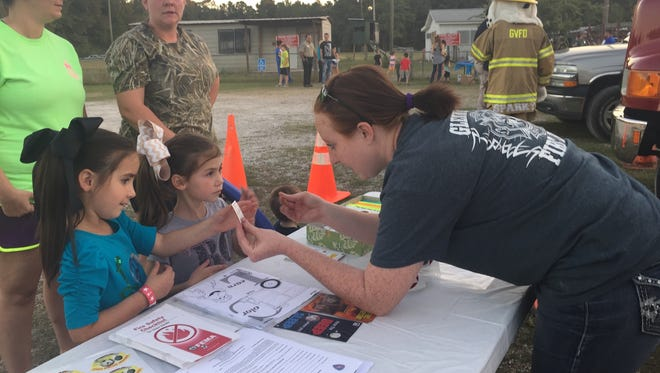Glenmora Volunteer Fire Department first responder Adrian Pace (right) hands stickers to Kaitlyn Verrett, 6, and Alexis Verrett, 4, on Tuesday at the Glenmora Police Department's National Night Out event.