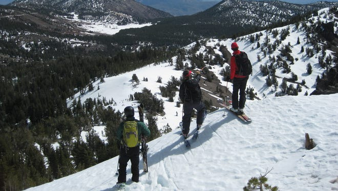 A trio of backcountry skiers on Rose Knob Peak in Washoe County, Nevada.
