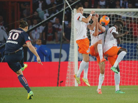 Paris Saint Germain's Zlatan Ibrahimovic, left, takes a free kick over the wall during his French League one soccer match against Montpellier , Saturday, May. 17, 2014, at the  Parc des Princes stadium, in Paris, France. (AP Photo/Jacques Brinon)
