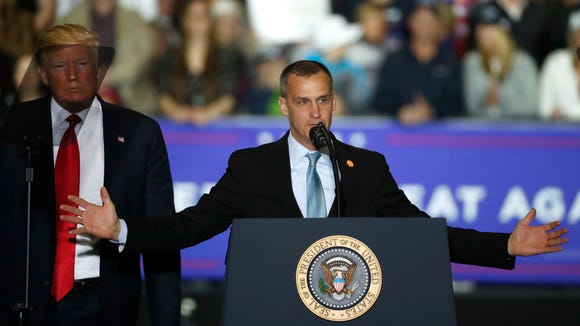 President Donald Trump, left, watches as Corey Lewandowski, right, his former campaign manager for Trump's presidential campaign, speaks during a campaign rally in Washington Township, Mich., Saturday, April 28, 2018.