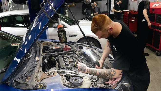 Klaben Ford auto technician Seth Grubich uses a light to get a good look at the engine in this Ford.