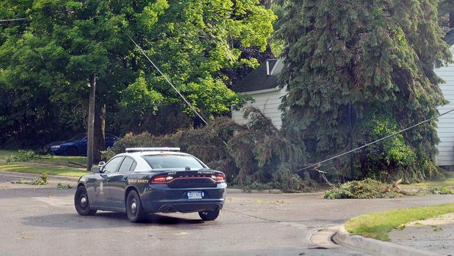 A Petoskey Department of Public Safety officer stands by the intersection of Bridge and Porter streets in Petoskey where a downed tree or large tree limb rests on top of a power line following a July 18 thunderstorm.