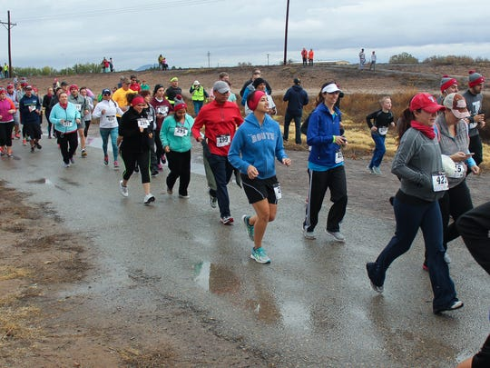 Participants in the Las Cruces Turkey Trot, held Thanksgiving morning at La Llorona Park, begin the 5K run. About 600 contestants participated in this year's race, despite the rainy weather.