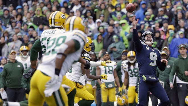 Seattle Seahawks' Jon Ryan throws a touchdown pass on a fake field goal attempt during the second half of the  NFC championship game Sunday against the Green Bay Packers.