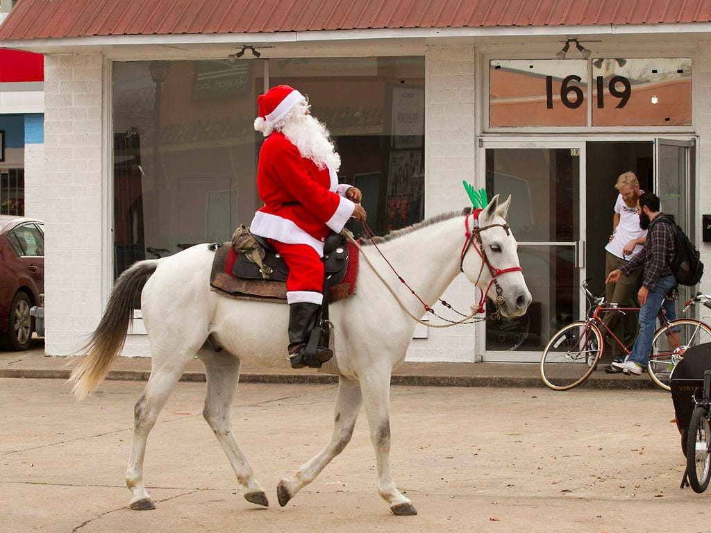 Sam Olivo, costumed as Santa Claus, rides his horse, Tex, along East Cesar Chavez Street on Dec. 10 in Austin, Texas.  Olivo said he was on his way to the Capitol to wave to motorists and spread Christmas cheer.