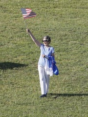 A woman waves the American flag to greet the passengers