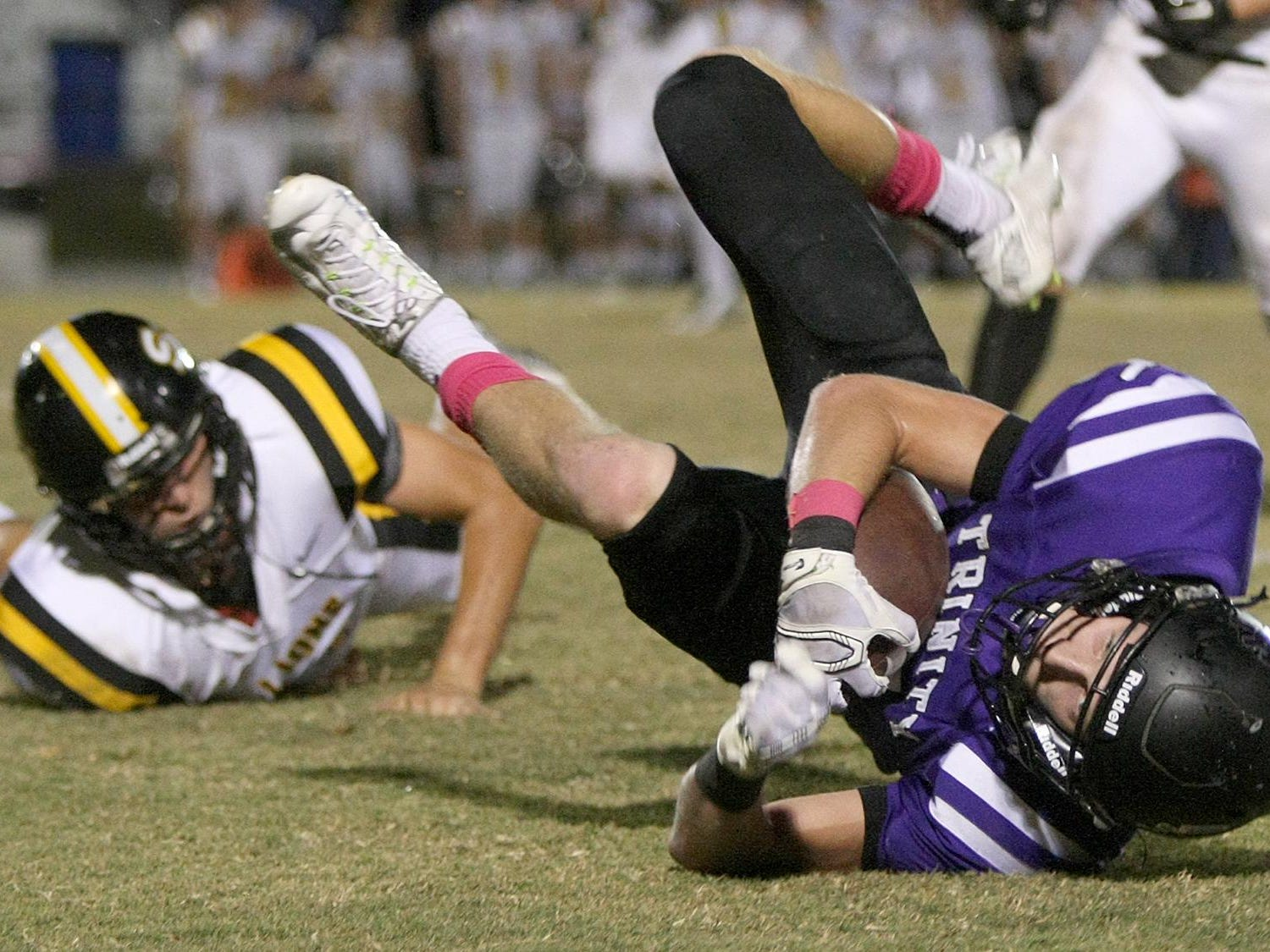 Trinity Christian Academy's Eli Parker (5) is tripped up by Scotts Hill's Michael Lyles (12) at TCA on Friday.