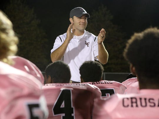 Liberty head coach Tyler Turner talks with his team after they defeated South Side 49-6 and finished the season 10-0.