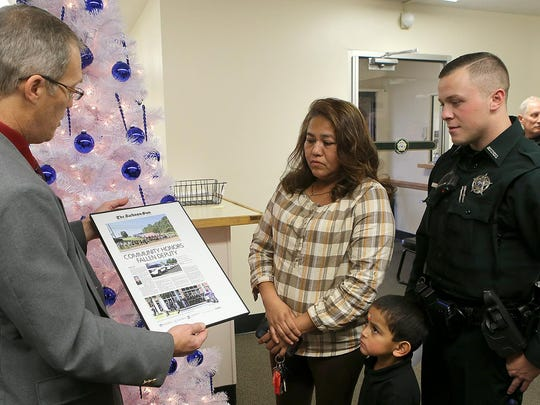 Steve Coffman, executive editor of The Jackson Sun, left, presents a commemorative page from the newspaper honoring Deputy Rosemary Vela to her mother Maria Vela, brother Isaac Vela and Madison County Deputy Dillon Wooley, Rosemary Vela's fiancé, at the Madison County Sheriff's Office on Thursday. Deputy Vela died in a car accident Sept. 28 while in the line of duty.