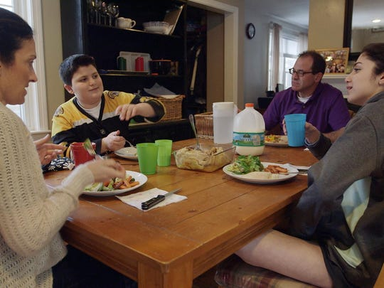 "This undated photo provided by Kikim Media shows the Scavotto family sitting down to dinner, in a scene from the documentary film, ""In Defense of Food."" Anthony, second left, was referred to a program for overweight kids at Boston Children's Hospital after gaining 30 pounds in one year. The film is based on Michael Pollan's book, ""In Defense of Food,"" and premieres on PBS on Dec. 30, 2015."