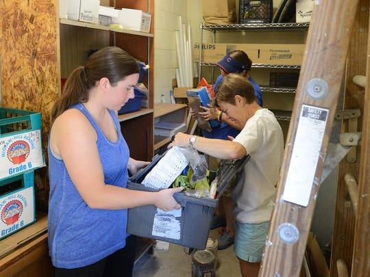 Jessica Gastelum, from left, Joanne Magyari and Jennifer Latham work on clearing out closet space for the Parent Teacher Organization on July 22 at East Elementary School. Gastelum and Magyari's children attended Nova Elementary School last year, but due to Vision 2020, their children will be attending East this year.