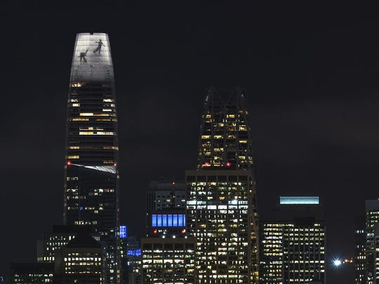 In this image depiction provided by LED artist Jim Campbell, the outline of two dancers captured mid-motion is displayed on the nine-story electronic art installation atop the $1.1 billion Salesforce Tower under construction in San Francisco.