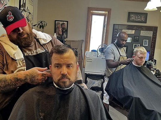 ABOVE: Johnny Interval, left, owner of the Barbiere, and barber Ed Williams tend to customers Jonathan Gottschall, left, and Trevor Rowland in Washington, Pa.