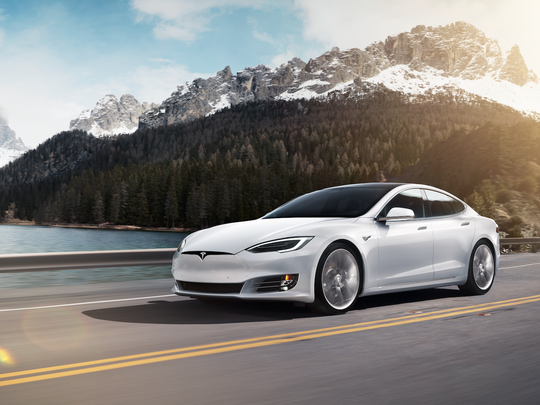 A white Tesla Model S car driving through the mountains.