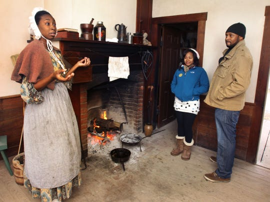 Janay Barksdale, left, a Conner Prairie interpreter tells visitors Ciara Wells and Eric Watkins, both Indianapolis, what it was like to be black and working in 1836. (2012 file photo)