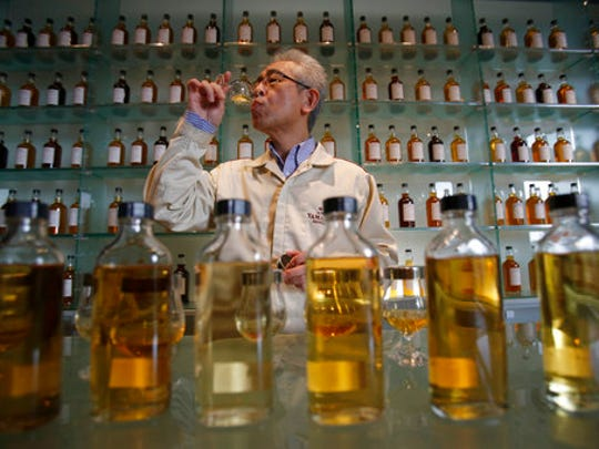 "In this March 8, 2017 photo, Suntory's chief blender Shinji Fukuyo demonstrates how he examines the whisky at the Suntory distillery in Yamazaki, near Kyoto, western Japan. ""What's important for whisky is that its deliciousness must deepen with aging, sitting in the casks for a long time,"" said Fukuyo, 55, demonstrating how he examines the whisky in a glass, swirling the crystalline amber spirit against the light."