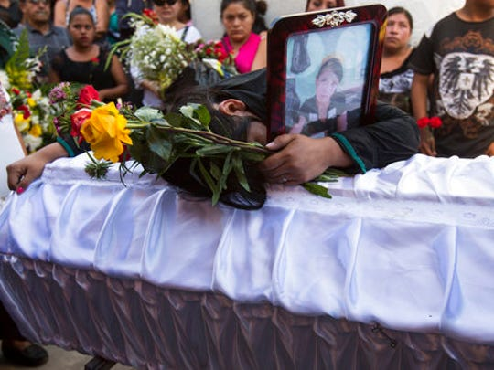 FILE - In this March 17, 2017 file photo, Shirley Palencia mourns over the coffin containing the remains of her 17-year-old sister Kimberly Palencia Ortiz, who died in the Virgen de la Asuncion Safe Home fire, at the cemetery in Guatemala City. Palencia Ortiz had been a ward of the state for nearly a year. Her father was in prison, her mother had disappeared, and her grandmother did not have the means to take care of her.