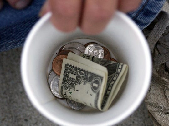 A panhandler shows his collection cup as he looks for some extra change along south Meridian Street.